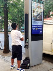 A man charges his phone at a Wi-Fi kiosk on Broadway at 86th Street in New York. The kiosk is part of a public-private partnership that offers free internet access, phone charging and domestic calls.
