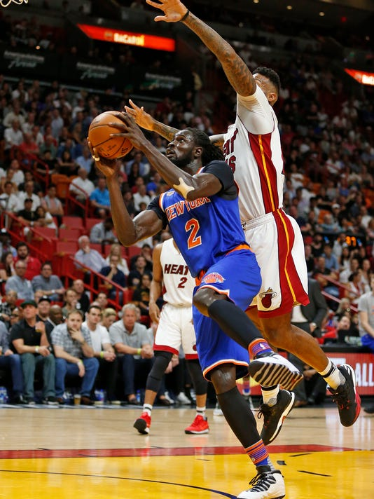 New York Knicks' Maurice Ndour (2) goes to the basket while being defended by Miami Heat's James Johnson (16) during the first half of an NBA basketball game, Friday, March 31, 2017, in Miami. (AP Photo/Joel Auerbach)