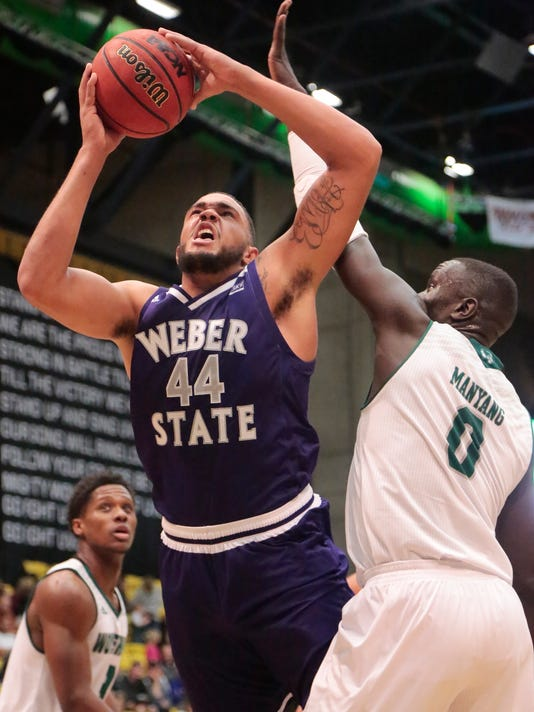 Weber State's Zach Braxton (44) is fouled by Utah Valley's Akolda Manyang (0) while going up for a layup during the first half of an NCAA college basketball game Wednesday, Dec. 6, 2017, in Orem, Utah. (Matt Herp/Standard-Examiner via AP)