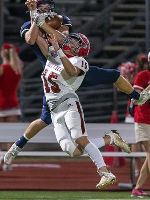 Wimberley wide receiver Nathan Simpson, left, pulls down a 35-yard reception over Fredericksburg defensive back Matthew Smith during the Texans' 21-20 win Friday. Simpson blocked a field goal, intercepted a pass and caught five passes for 80 yards in the victory.