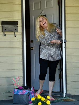 """Shaun Vrana, of Salina, opens her front door to realize she's received a gift basket from an anonymous person who was a member of the Salina-based """"Wine & Dash With Friends"""" Facebook group.  """"I truly needed this today. I was having a bad day,"""" said Vrana."""