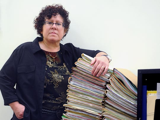 Jenny Salimbene, director of the Dutchess County Chemical Dependency Clinic at the Lexington Center for Recovery, Inc., stands next to large stacks of closed patient files in the organization's main office in the Town of Poughkeepsie. Files are closed after patients successfully complete their recovery from drug addiction.
