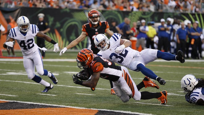 Cincinnati Bengals running back Jeremy Hill (32) is tackled by the Indianapolis Colts free safety Colt Anderson (32) on the half yard line in the second quarter during their preseason game at Paul Brown Stadium.