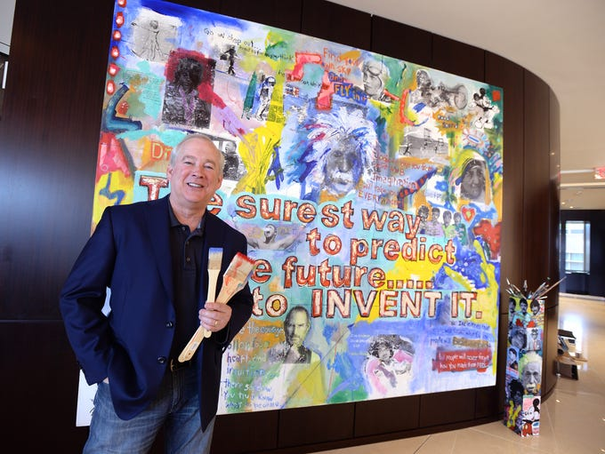 """Joe Erwin stands in front of the painting """"The Quote"""""""