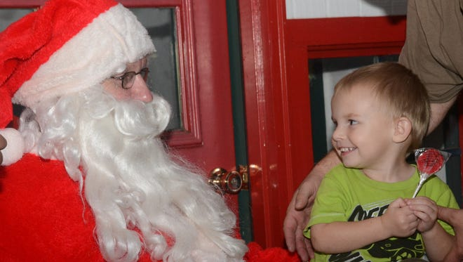 Quentin Rush, 2, grins while meeting Santa Claus last year in downtown Alexandria.