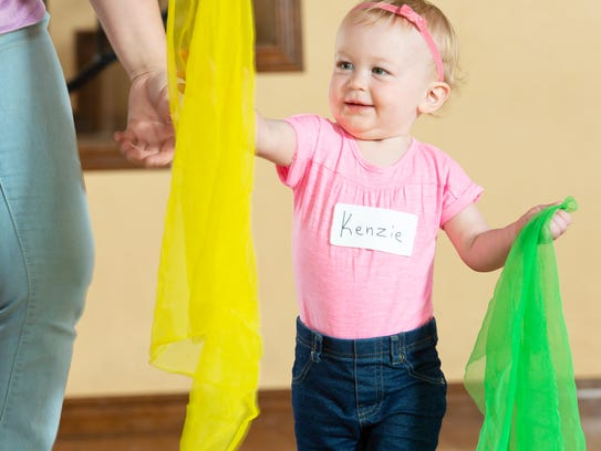 Kenzie Wing, 18 months-old, plays with colorful scarfs with her mother, Chelsea Wing, during a Zumbini class at La Buena Vida Women's Club in April.