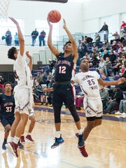Andrew Wells of East Lansing goes up for a layup against