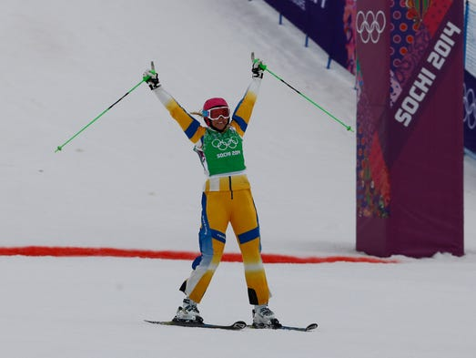 Anna Holmlund (SWE, green) crosses the finish line in the semifinals for ladies' ski cross during the Sochi 2014 Olympic Winter Games at Rosa Khutor Extreme Park.