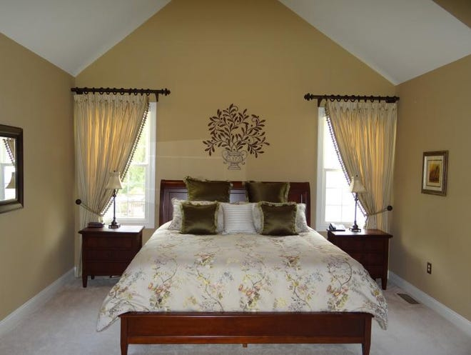 Kennett Square, Pa., interior decorator Mary Cairns recommends investing in quality bed linens to create a romantic refuge like this Glen Mills, Pa., master bedroom with bed in a bag and custom drapes.