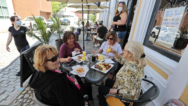 In this June file photo, patrons return to eat at Tia Maria's European Cafe in downtown New Bedford after it opened its outdoor seating area for the first time.