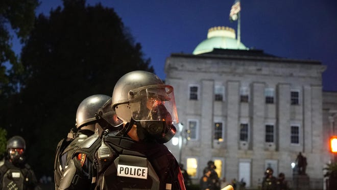 Police in riot gear protect the old state capitol building in Raleigh Sunday. It was the second day of protests in the North Carolina capital following the death of Minnesotan George Floyd while in police custody.