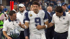Cowboys QB Tony Romo is helped off the field Thursday