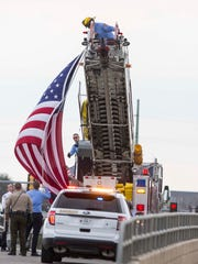 Pleasant Hill Firemen raise a flag on University Ave on overpass over I-80/I-35 to pay respects to police officer Susan Farrell, Des Moines Police Dept. Wednesday, March 30, 2016.