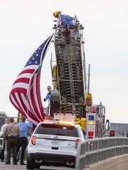 Pleasant Hill Firemen raise a flag on University Ave
