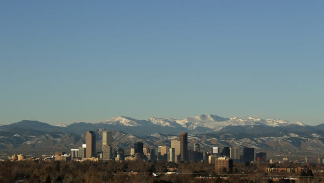In this Jan. 24, 2016, file photo, the Rocky Mountains rise beyond the Denver skyline.