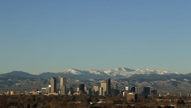 FILE - In this Jan. 24, 2016 file photo, the Rocky Mountains rise beyond the Denver skyline.