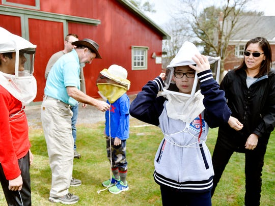 Jonathan Chang, 11 of Hampden Township, Cumberland County, adjusts his beekeeper's hat and veil before venturing with his FIRST LEGO League teammates to the bee hives belonging to Jeremy Barnes, second from left, who is adjusting a beekeeper's veil for Kellen Conway, 10 of Hampden Township, Sunday, April 2, 2017, at Barnes' Meadowsong Farm Apiary in Springfield Township. A Harrisburg-area FIRST LEGO League team of students came to see whether powdered sugar would irritate varroa mites off a hive of honeybees and yield a mite count on the hive's bottom board that they could detect with an infrared camera. The experiment was part of a STEM-driven challenge for which the students will go to St. Louis, Mo., at the end of the month.
