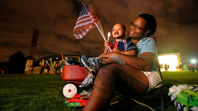 In this file photo, Tiana McWhite and her son Landry McWhite watch the fireworks show at the Riverwalk in Montgomery, Ala. on Thursday evening July 4, 2013. (Montgomery Advertiser, Mickey Welsh)