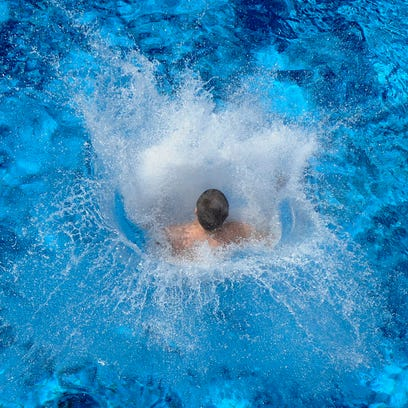 Water splashes as a teenager jumps into a  public pool