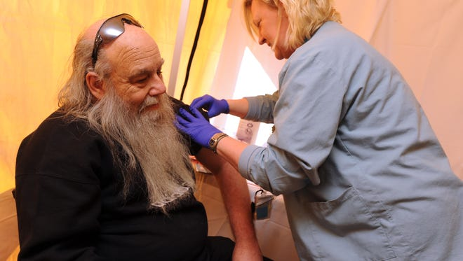 Registered Nurse Timea Takacs gives Air Force veteran George McGill of Pensacola a flu shot inside the medical tent on Friday morning at the 2013 Homeless Veterans Stand Down at the Joint Ambulatory Care Center next to Pensacola Naval Hospital.