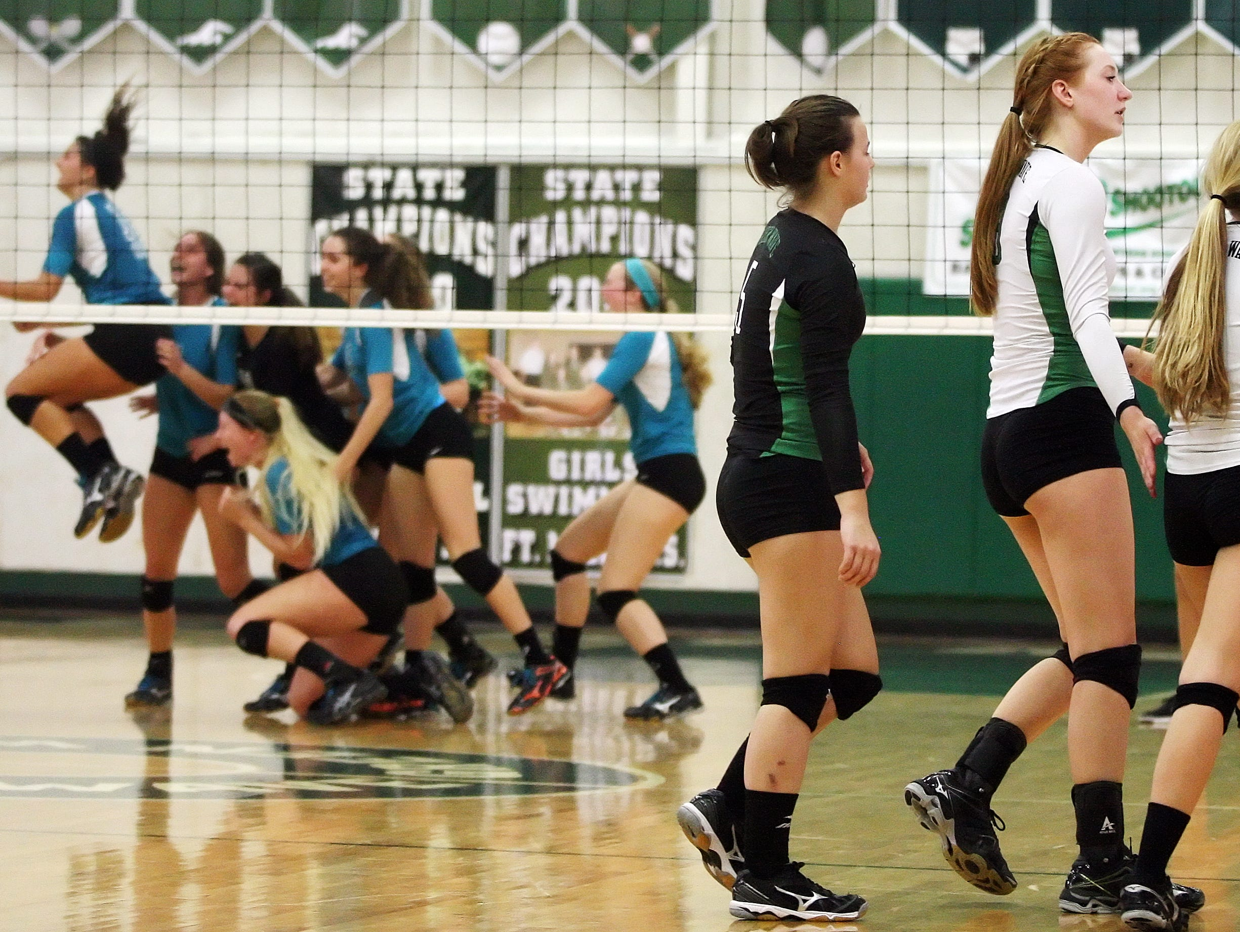 Fort Myers High School's Casey Adams, center, Kaitlin Stewart and Sydney Green leave the court as Jensen Beach celebrates winning the Class 6A volleyball semifinals Saturday at Fort Myers High School.