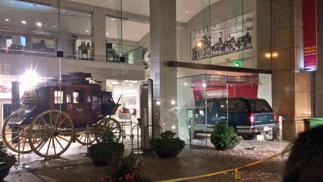 A vehicle is seen smashed into the window of the Wells Fargo History Museum in downtown San Francisco, Tuesday, Jan. 27, 2015. Thieves in the SUV smashed through the glass doors of the museum and made off with gold nuggets on display.