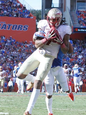 Florida State wide receiver Kelvin Benjamin (1) catches the ball over Florida defensive back Vernon Hargreaves III (1) during the second half Saturday at Ben Hill Griffin Stadium.