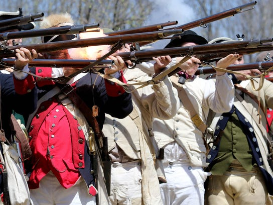 Continental soldiers take aim and fire during a military drill and firing demonstration at Jockey Hollow Morristown National Historical Park.