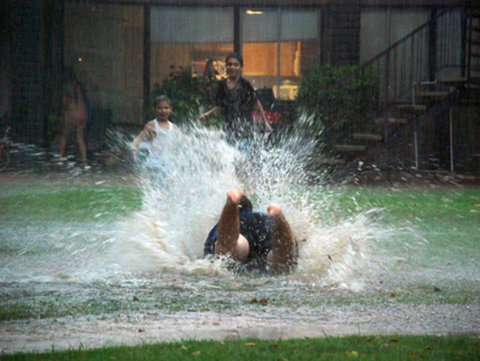 RAIN: Children playing in the rain in Tempe.