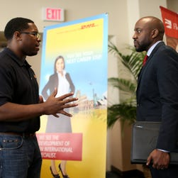 Jonathan Danner, a recruiter for DHL, left, speaks with U.S. military veteran Arlington Robertson as he explains the jobs available during the Veterans Career and Resource Fair hosted by Florida International University and the Miami Vet Center on Feb. 6, 2015 in Miami.