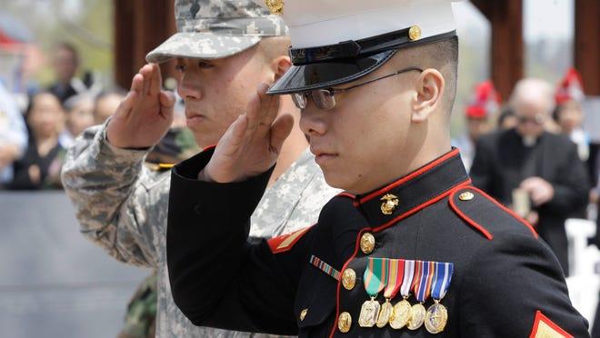 Servicemen render salutes at the Sheboygan Hmong Memorial during 2013's Memorial Day ceremony at Deland Park.