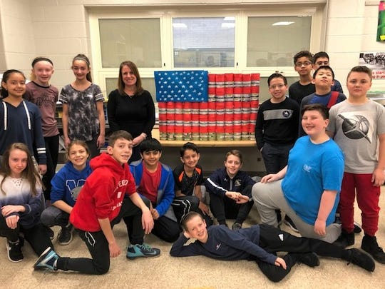 Mrs. Gina Banks' sixth-grade class poses with its American Flag can creation. Back row, from left: Arianne Hernandez, Madelyn Archibold, Alexa Christou, Mrs. Gina Banks,  Lance Garcia, Sohum Mehta, David Li, Timmy Velazquez. Sitting, from left: Daniella Aguiar, Julianna O'Sheal, Omar Saad, Karthik Sekhar, Aidan Law, Scott Drews, Jackson Scala (in blue, kneeling bottom right) and Robert Dufek (laying across the floor).