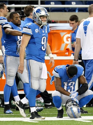 Detroit Lions quarterback Matthew Stafford (9) and receiver Nate Burleson react to a loss Dec. 16, 2013, at Ford Field in Detroit.