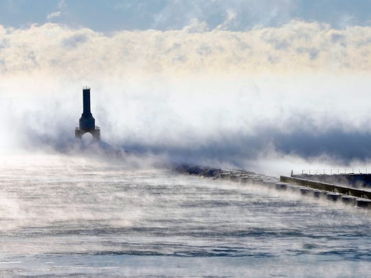 Steam rises around the Port Washington Lighthouse on Lake Michigan on January 18, 2016.