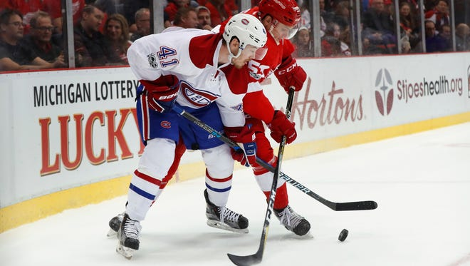 Montreal Canadiens left wing Paul Byron and Detroit Red Wings defenseman Alexey Marchenko battle for the puck in the third period of a game on Jan. 16, 2017, in Detroit.