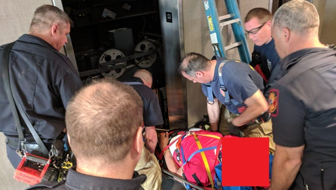 Wilmington emergency crews rescue man from elevator that fell as much as 8 feet. Firefighters blocked out the victim's face.