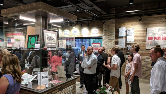 Twin Disc employees take a first look at the Heritage gallery during the company's ribbon cutting ceremony Thursday afternoon.