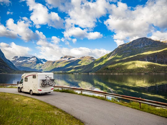 An RV on a road in front of mountains and a lake.