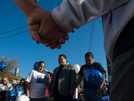 Gatherers hold hands as pastor Adrian Arce, center,