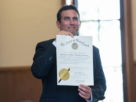 Matthew Maciarello, holds a certificate during his