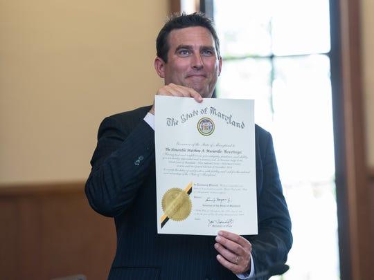 Matthew Maciarello, holds a certificate during his