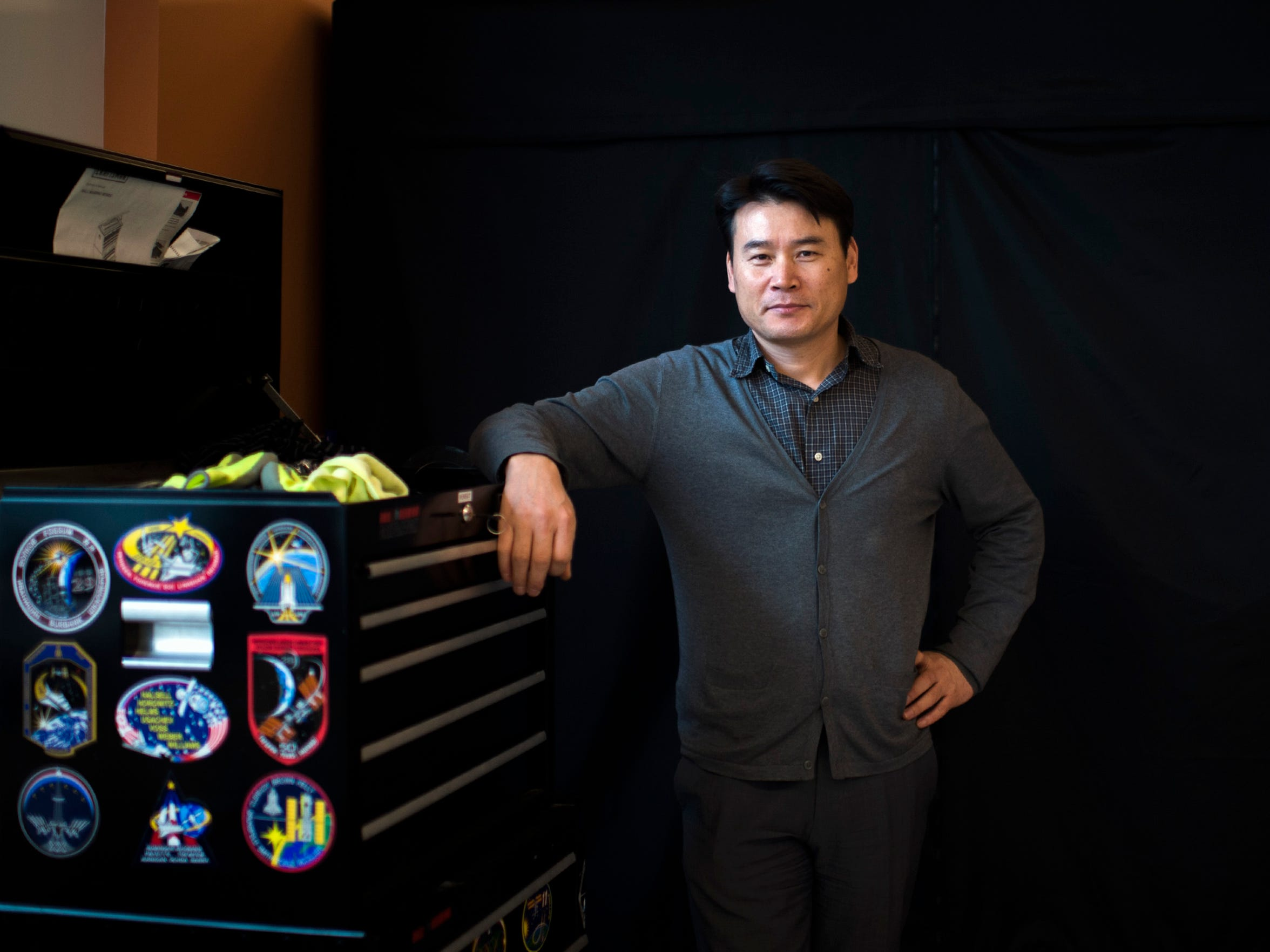 Assistant Professor and the project's principal investigator Sangho Shin poses inside the lab as students work on the construction of the CubeSat.