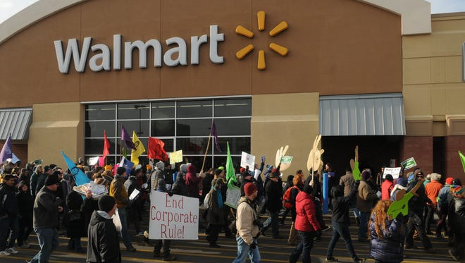 Protestors stream past the entrance to a Walmart store on Universty Avenue in St. Paul, Minn. on Black Friday, Nov. 29, 2013. A judge ruled Thursday that Walmart violated labor relations law when it fired a group of workers who participated in strikes in May and June of 2013.