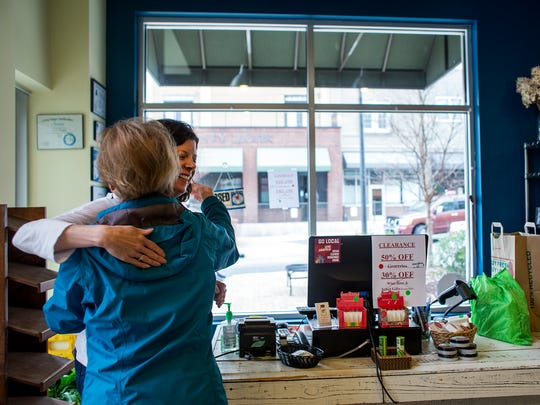 Livi's Pantry owner Missy Culver receives a hug from YMCA employee and customer Diane Saccone on Culver's last day of business in Reynolds Village.