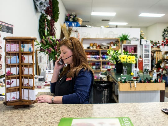 Kaylynne Allen, of Kaylynne's Briar Patch Florist, helps a customer over the phone at her shop in Reynolds Village. Allen moved her 27-year-old business into the community in June. She said her customer base is helping her keep her business up, and she hopes Reynolds Village will bring her more patrons.