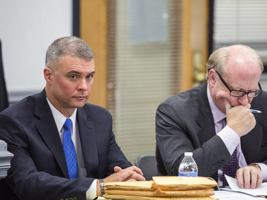 Then-Lt. Mark Byrd and his attorney, John Hunter, sit at the Civil Service Board meeting at Asheville City Hall on Nov. 19, 2014. Byrd and Hunter say he was transferred to an administrative job after raising concerns about downtown staffing. Byrd's grievance later was dismissed on grounds he missed the filing deadline.