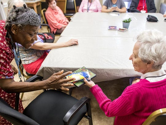 Maggie Belle Gladden, left, gives a gift to Mary Ida Sprague during Jewish Family Services' Elder Club last month. Elder Club is a group socialization and caregiver respite program that was established in 1999 to serve older adults who are isolated and in need of social contact.