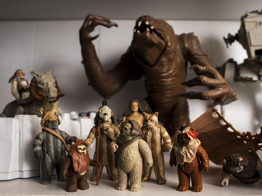 "Ewok figurines and other characters stand arranged on shelves in Pat Douglas' basement. Douglas has been receiving ""Star Wars"" toys since he was 2 and collecting them since he was 5. Today, he has at least a thousand pieces in and out of packaging."