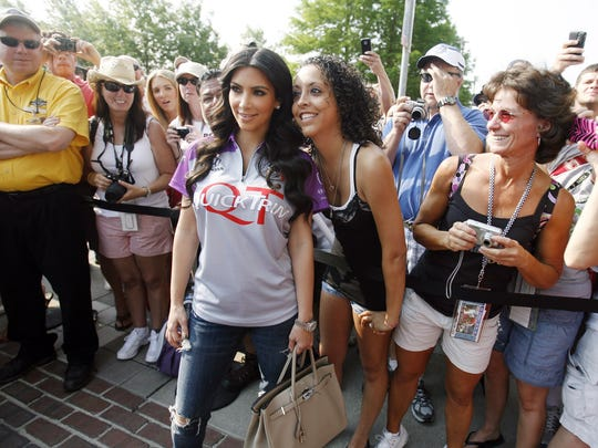 Kim Kardashian poses with a fan before the 2010 Indianapolis 500.