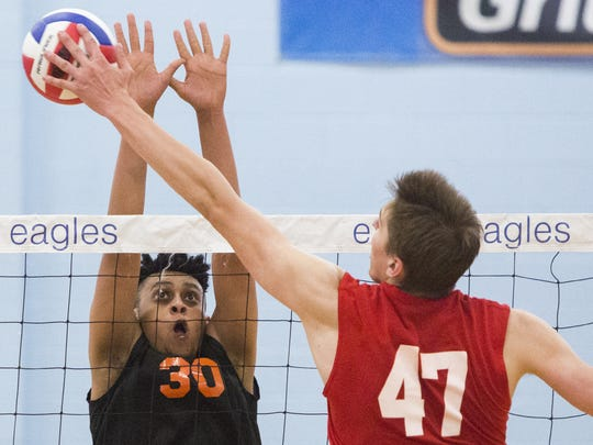 York Suburban's David Kinfe defends the net as Holy Redeemer's Rob Zbierski hits the ball. York Suburban defeats Holy Redeemer 3-2 in the quarterfinals of the PIAA Class AA boys' volleyball state championships at Exeter Township Senior High School, Saturday, June 4, 2016.